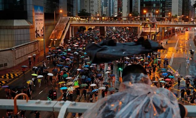 A person holding a broken umbrella observes anti-extradition bill protesters marching to demand democracy and political reforms, in Hong Kong, China August 18, 2019. REUTERS/Tyrone Siu