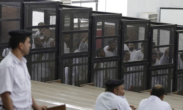 "Islamist defendants stand behind bars in the case known as the ""Kerdasa massacre'', that referred 188 people to court over an attack that killed 14 policemen in 2013, in Cairo June 23, 2014/REUTERS"