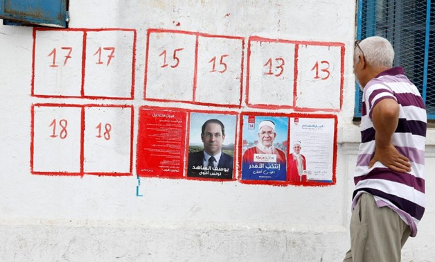 A man looks election posters of presidential candidates in Tunis, Tunisia September 2, 2019. REUTERS/Zoubeir Souissi