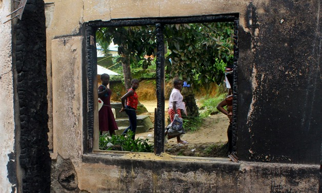 People are seen through the charred window of a building after a fire swept through a school killing children in Monrovia, Liberia September 18, 2019. REUTERS/Stringer.