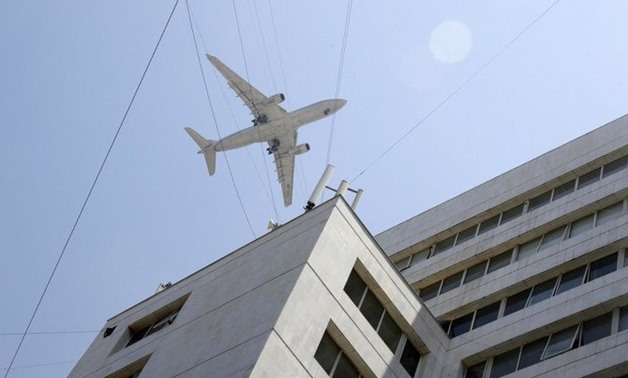 Above, an Etihad Airways aircraft crosses at low altitude above buildings in the Lebanese capital Beirut's coastal neighborhood of Hamra on July 10, 2019. (AFP)