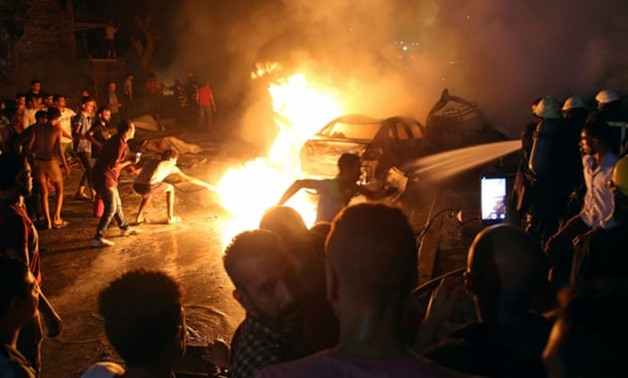 Civilians try to extinguish a fire from the blast outside the hospital. Shokry Hussein/Reuters