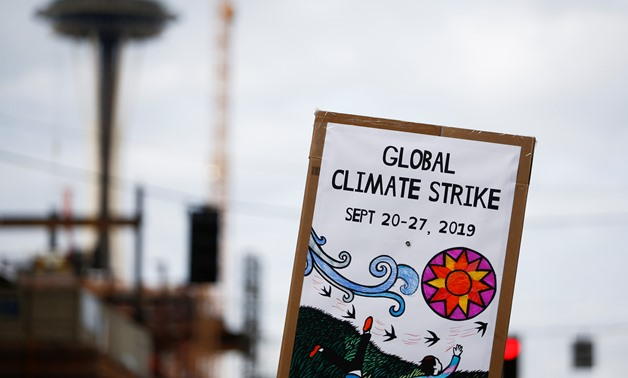 A tech worker holds a climate strike sign with the Space Needle seen in the background during a Climate Strike walkout and march in Seattle, Washington, U.S. September 20, 2019. REUTERS/Lindsey Wasson