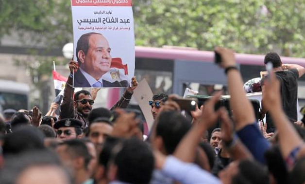FILE - Protesters hold poster of Egyptian President Abdel Fattah al-Sisi in front of the Syndicate of Journalists, in Cairo, Egypt May 4, 2016 - Reuters