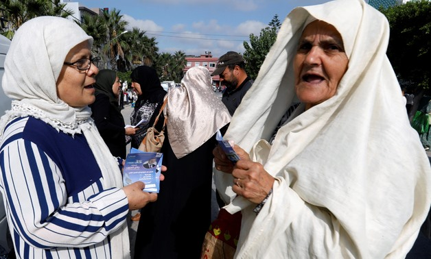 A supporter of Tunisia's moderate Islamist Ennahda party, talks with a woman while distributing election leaflets for the upcoming parliamentary elections in the hilltop town of al-Alia, Tunisia September 30, 2019. Picture taken September 30, 2019. REUTER