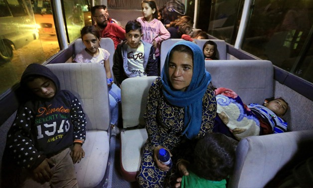 Syrian displaced families, who fled violence after the Turkish offensive against Syria, sit in a bus after arrival at a refugee camp in Bardarash on the outskirts of Dohuk, Iraq October 17, 2019. REUTERS/Ari Jalal