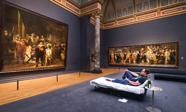Lucky Stefan Kasper lying on a bed in front of the painting The Night Watch  by Dutch painter Rembrandt at Amsterdam's Rijksmuseum  - AFP