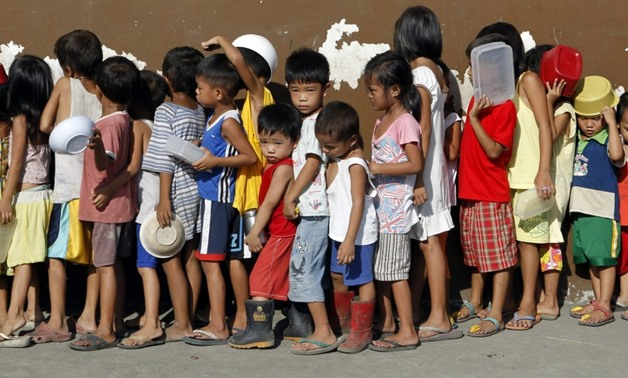 Children queue for free porridge at a local government feeding program in Tondo, Manila, Oct. 29, 2011. REUTERS/Erik De Castro