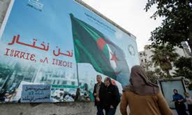 People walk past a campaign poster for presidential election in Algiers, Algeria November 2, 2019. REUTERS/Ramzi Boudina