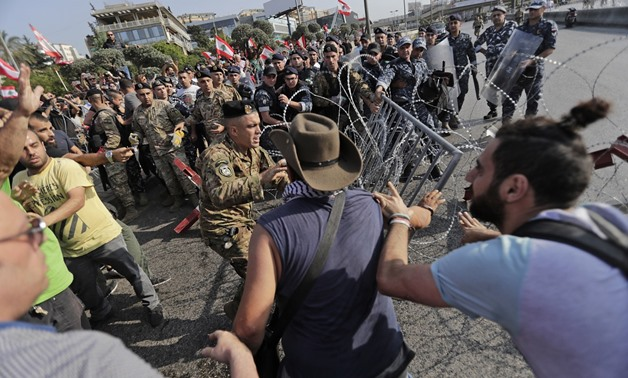 Lebanese demonstrators try to remove the barbed-wire and metal rail, placed by anti-riot police (background), on the road leading to the Presidential Palace in Baabda, on the eastern outskirts of Beirut on November 13, 2019. ANWAR AMRO / AFP