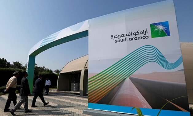 FILE PHOTO: The logo of Aramco is seen as security personnel walk before the start of a press conference by Aramco at the Plaza Conference Center in Dhahran, Saudi Arabia November 3, 2019. REUTERS/Hamad I Mohammed/File Photo