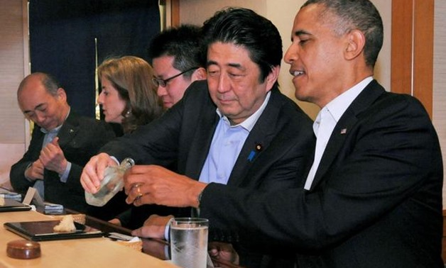 FILE PHOTO : Japanese Prime Minister Shinzo Abe pours sake for U.S. President Barack Obama as they have dinner at the Sukiyabashi Jiro sushi restaurant in Tokyo, in this picture taken April 23, 2014, and released by Japan's Cabinet Public Relations Office