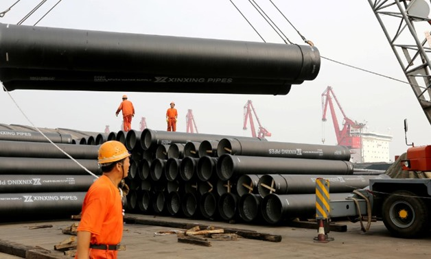 FILE PHOTO: Workers direct a crane lifting ductile iron pipes for export at a port in Lianyungang, Jiangsu province, China June 30, 2019. REUTERS/Stringer