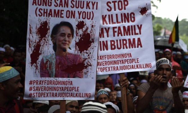 Ethnic Rohingya Muslim refugees hold placards, many with portraits of Aung San Suu Kyi and shout slogans during a protest against the persecution of Rohingya Muslims in Myanmar, outside the Myanmar Embassy in Kuala Lumpur on Friday. AFP/MANAN VATSYAYANA