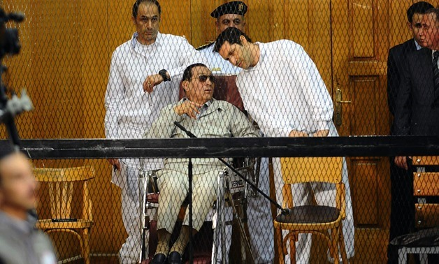 FILE-Egyptian toppled president Hosni Mubarak and his two sons Alaa (R) and Gamal stand behind bars during their trial at the Police Academy on September 14, 2013 in Cairo. AFP PHOTO / AHMED EL-MALKY