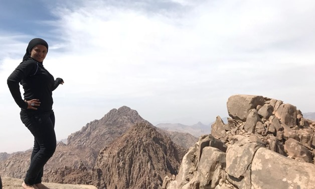 "Mai Adel on the top of Rimhan Mountain, South Sinai, in March 2018. Adel likes to take a picture with bare feet at the top of every mountain she climbs to ""feel the energy of the place"" unless it is too cold."