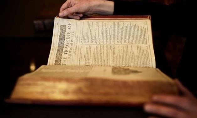 FILE PHOTO: A worker poses with a first edition of the First Folio, the first collected edition of William Shakespeare's works, containing 36 plays, at Christie's auction house in London, Britain April 19, 2016. REUTERS/Dylan Martinez/File Photo