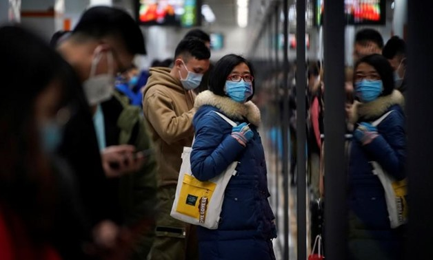 People wearing masks are seen at a subway station in Shanghai, China January 23, 2020. REUTERS/Aly Song