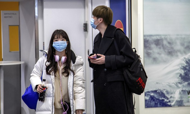 Air travellers wear masks as they arrive at Ivalo Airport, Finland January 24, 2020. On Thursday, two tourists visiting Finland from Wuhan, China went to a health centre in Ivalo, seeking treatment for flu-like symptoms. The tourists are suspected of bein