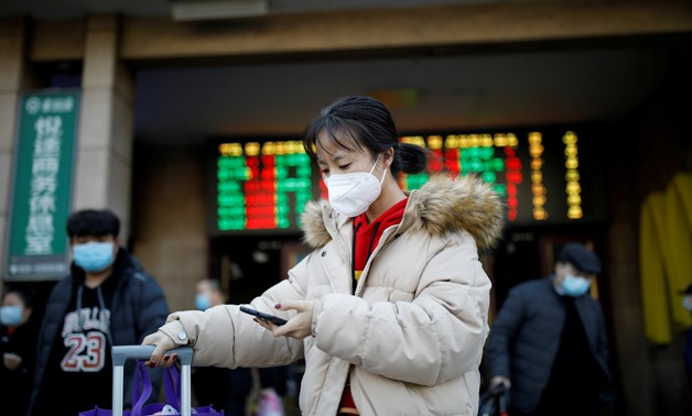 A woman wearing a face mask uses her cellphone as she walks outside Beijing Railway Station as the country is hit by an outbreak of the new coronavirus, in Beijing, China January 30, 2020. REUTERS/Carlos Garcia Rawlins