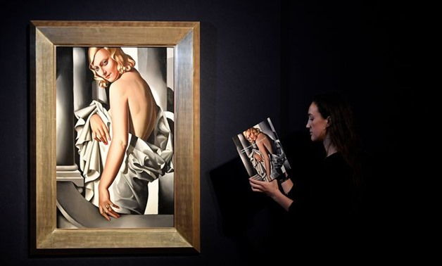 An employee poses as she views a sales catalogue next to 'Portrait de Marjorie Ferry' by Tamara de Lempecka ahead of Impressionist, Modernist and Surreal sales at Christie's auction house, London, Britain, January 30, 2020. REUTERS/Toby Melville