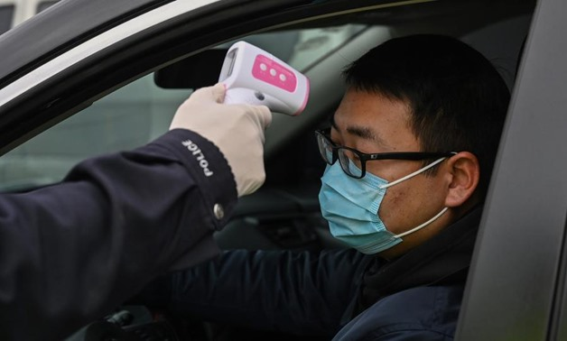 A police officer takes the temperature of a driver at a checkpoint on a street on the outskirts of Wuhan in China's central Hubei province on January 27, 2020, amid a deadly virus outbreak which began in the city. Photo: AFP/Hector Retamal