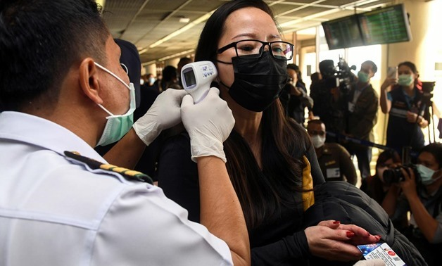 A health worker uses an infrared thermometer to check the temperature of a tourist who arrives at Bangkok's Don Mueang Airport, Thailand, January 25, 2020. REUTERS/Panumas Sanguanwong