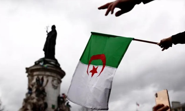 FILE - An Algerian protester waves the national flag - Reuters