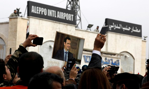 People hold up a picture of Syria's President Bashar al-Assad at Aleppo international airport, after the airport was reopened for the first time in years, Syria February 19, 2020. REUTERS/Omar Sanadiki