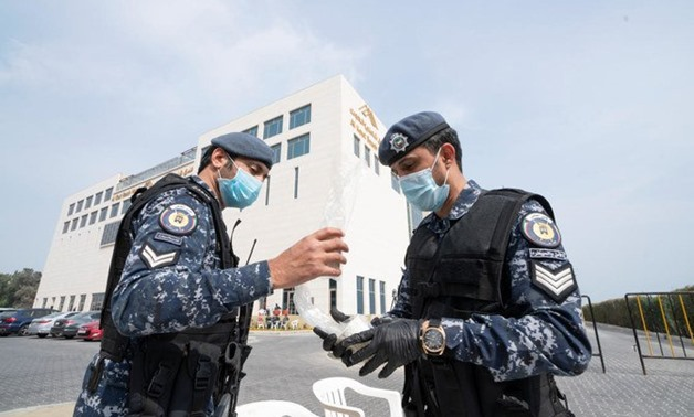 FILE - Kuwaiti police wearing masks after several people were infected with coronavirus in Kuwait - Reuters