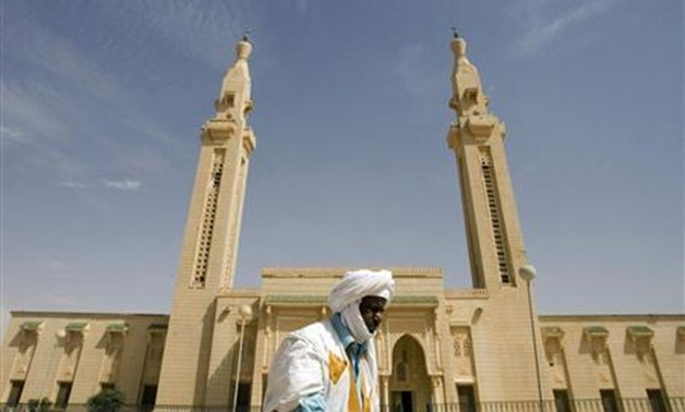 Mauritanian old man walking past a mosque - Reuters