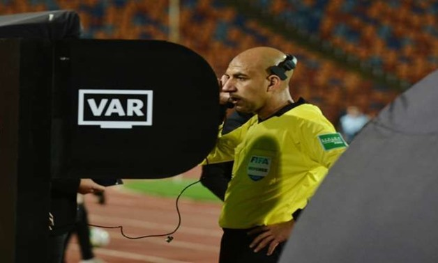 Egyptian referee, Mohamed Adel, reviews a penalty case decision during Al Ahly clash against Smouha