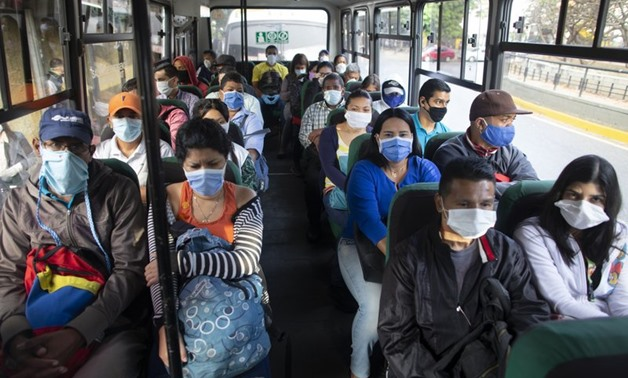 People wearing protective masks as a precaution against the spread of the new coronavirus travel on a bus in Caracas, Venezuela, Tuesday, March 17, 2020. President Nicolas Maduro ordered citizens to stay home, and to wear a mask in public under a quaranti
