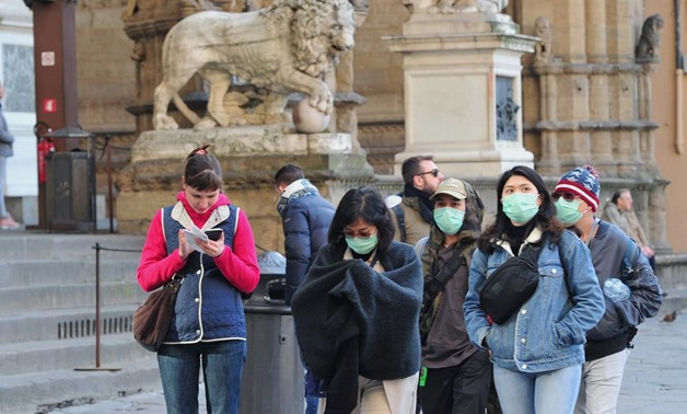 People wearing protective masks walk through Florence as Italy battles a coronavirus outbreak, in Florence, Italy, March 7, 2020. REUTERS/Jennifer Lorenzini
