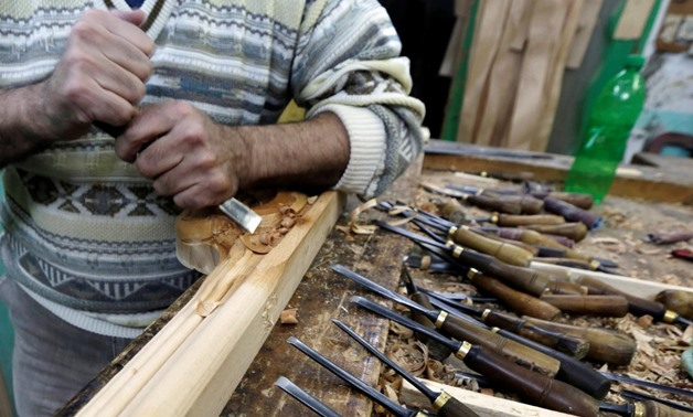 An Egyptian craftsman handles wood parts for furniture at his workshop in the city of Damietta, Egypt January 14, 2020. Picture taken January 14, 2020. REUTERS/Hayam Adel