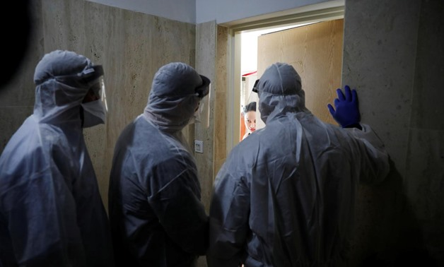 Health Ministry inspectors speak with a woman who is in self quarantine as a precaution against coronavirus spread in Hadera, Israel March 16, 2020 REUTERS/Ronen Zvulun