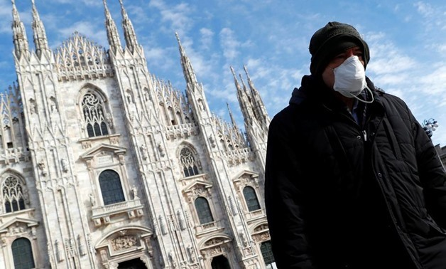 A man wearing a protective face mask to prevent contracting the coronavirus walks past the Duomo Cathedral in Milan, Italy, March 4, 2020. REUTERS/Guglielmo Mangiapane
