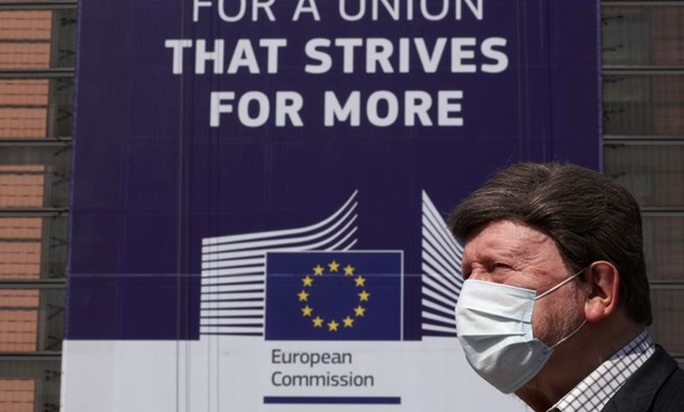 A man wearing a face mask walks past the European Commission headquarters as the spread of coronavirus disease (COVID-19) continues in Brussels, Belgium April 9, 2020. REUTERS/Yves Herman
