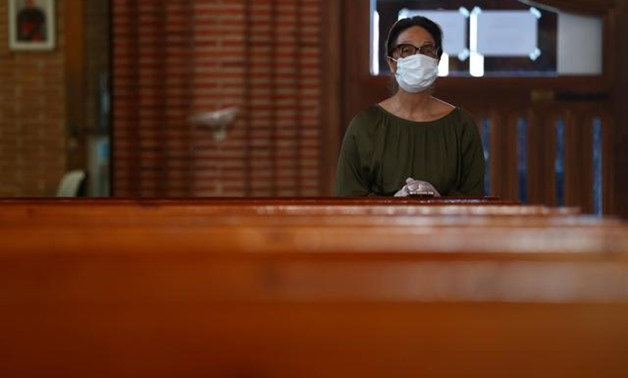A woman kneels as she prays after Easter Sunday mass at a empty Santa Maria de Cana parish amid the coronavirus disease (COVID-19) outbreak in Pozuelo de Alarcon, Spain, April 12, 2020. REUTERS/Sergio Perez