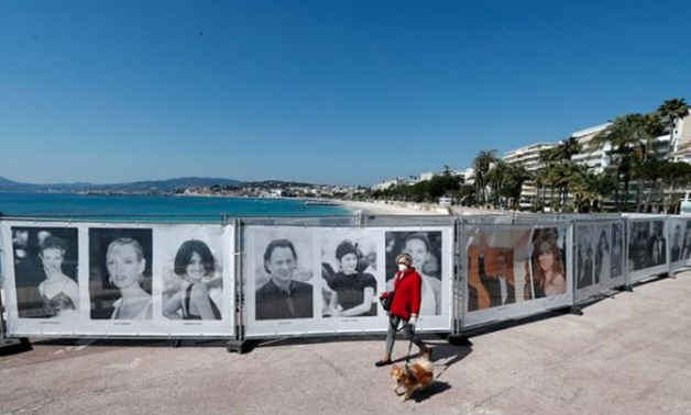 FILE PHOTO: A woman walks past photos of the Cannes Film festival on the Croisette in Cannes as a lockdown is imposed to slow the rate of the coronavirus disease (COVID-19) in France, March 18, 2020. REUTERS/Eric Gaillard/File Photo