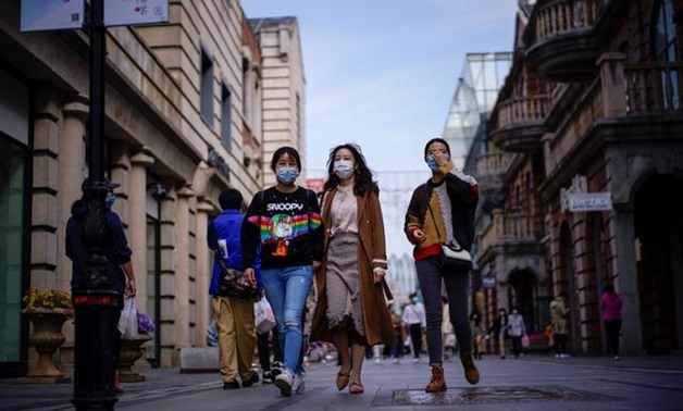 FILE PHOTO: People wearing face masks are seen at a main shopping area after the lockdown was lifted in Wuhan, capital of Hubei province and China's epicentre of the novel coronavirus disease (COVID-19) outbreak, April 14, 2020. REUTERS/Aly Song