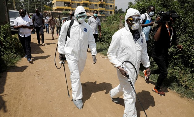 Kenyan health workers dressed in protective suits walk after disinfecting the residence where Kenya's first confirmed coronavirus patient was staying, in the town of Rongai near Nairobi, Kenya March 14, 2020. REUTERS/Baz Ratner
