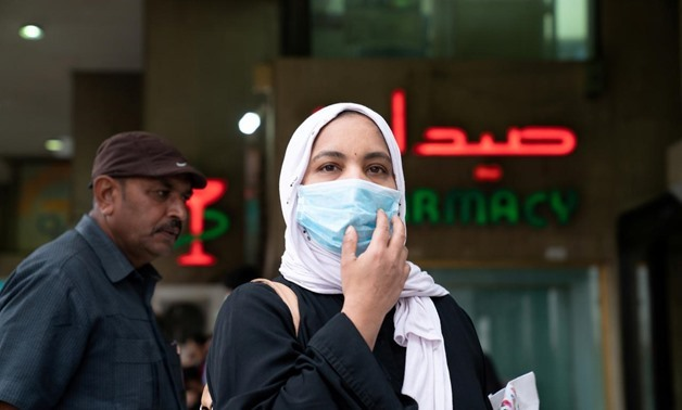 FILE - A woman wears a protective face mask, following the outbreak of the new coronavirus, in Kuwait, February 25, 2020 - Reuters/Stephanie McGehee