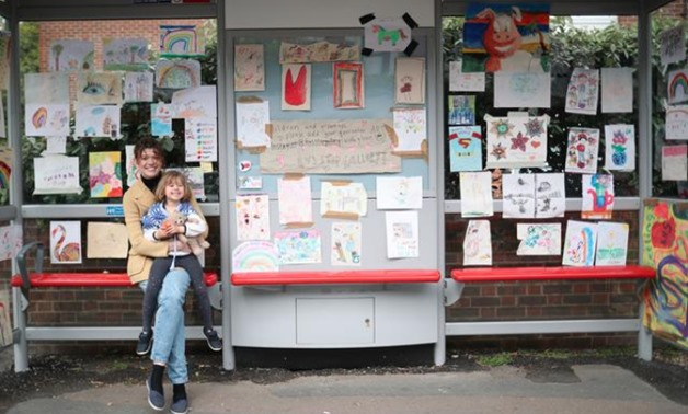 """Sarah Lamarr and her 4 year old daughter, Rosie, who started a """"Bus stop gallery"""" pose for a photograph at a bus stop with art work following the outbreak of the coronavirus disease (COVID-19), London, Britain, April 27, 2020. REUTERS/Hannah McKay"""