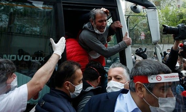 A demonstrator, wearing a face mask for protection against coronavirus, reacts after his arrest by Turkish police officers, during May Day protests in Istanbul, on May 1, 2020. (AP)