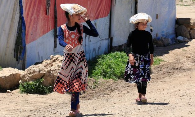Syrian refugee girls carry stacks of bread on their heads, as Lebanon extends a lockdown to combat the spread of the coronavirus disease (COVID-19) at a Syrian refugee camp in the Bekaa valley, Lebanon May 7, 2020. REUTERS/Ali Hashisho
