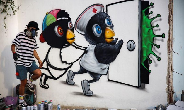 Mue Bon, a Thai street artist paints a mural depicting characters attempting to keep a virus at bay, in Bangkok, amidst an outbreak of the coronavirus disease (COVID-19) in Thailand, May 21, 2020. REUTERS/Juarawee Kittisilpa.