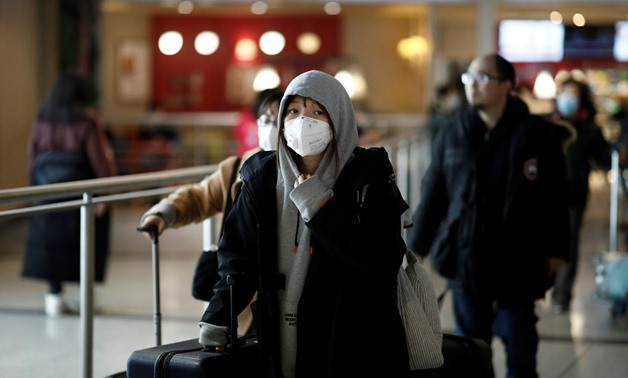 FILE PHOTO: Tourists from an Air China flight from Beijing wear protective masks as they arrive at Charles de Gaulle airport in Paris, France, January 26, 2020. REUTERS/Benoit Tessier