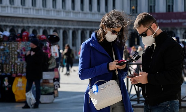 Tourists wear protective masks in Saint Mark's Square in Venice as Italy battles a coronavirus outbreak, Venice, Italy, February 27, 2020. REUTERS/Manuel Silvestri