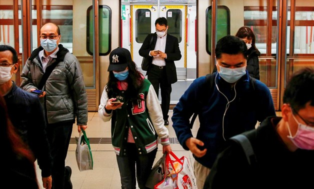 FILE PHOTO: People wear protective masks following the outbreak of a new coronavirus, during their morning commute in a station, in Hong Kong, China February 10, 2020. REUTERS/Tyrone Siu/File Photo